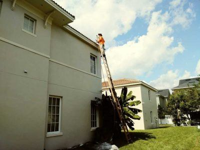 Man pressure washing an apartment building roof